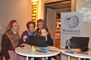 """Staff member Sophie Österberg in a demonstration of Wikipedia for members of Sorunda ward association in traditional dresses on the day of the fifth anniversery of Wikimedia Sweden. """"Hembygdens helg 2012 02"""" by Axel Pettersson, under CC-BY-SA 3.0 Unported, from Wikimedia Commons"""